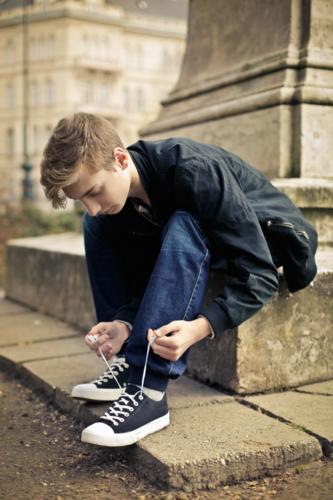 Joven atando cordones de su calzado juvenil Chikihuellas
